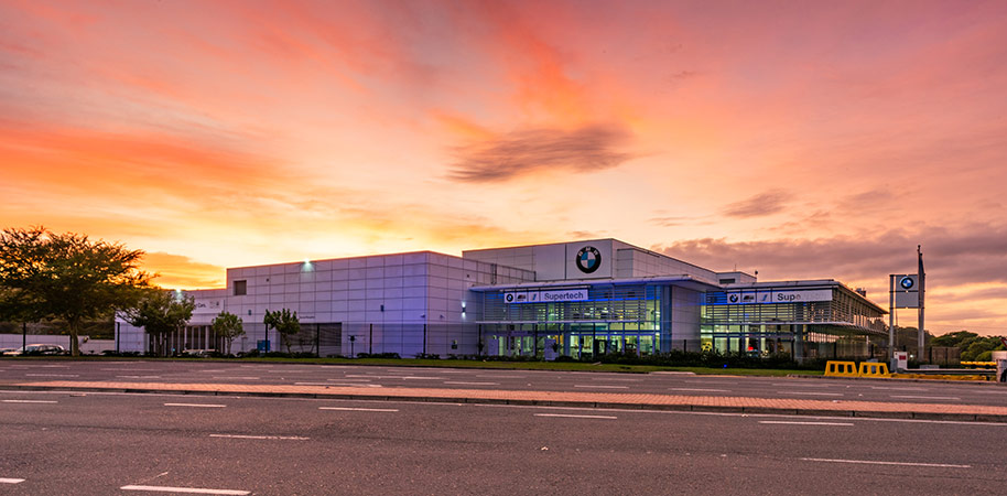 BMW car dealership from street view with pink sunrise
